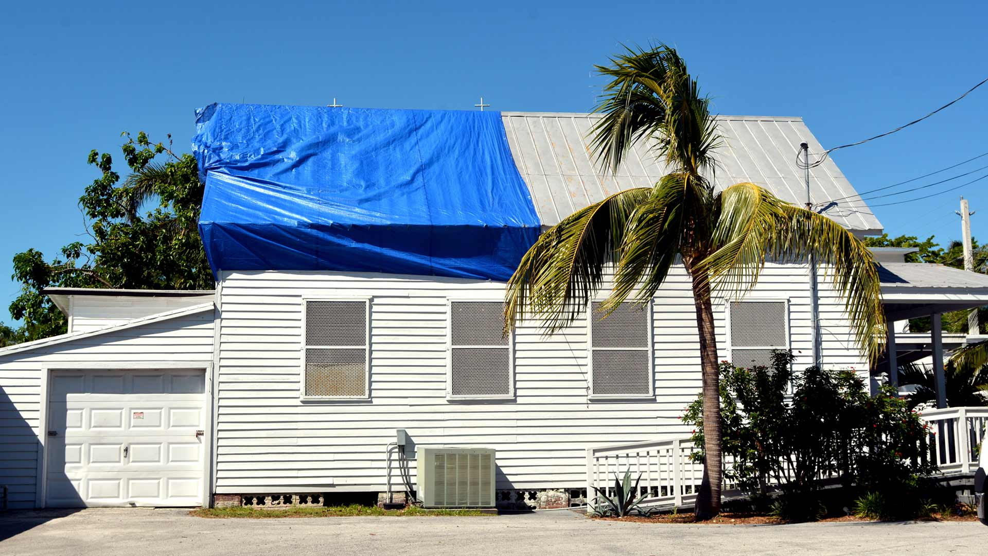 A home in Lakeland, FL with a tarp covering roof damage.
