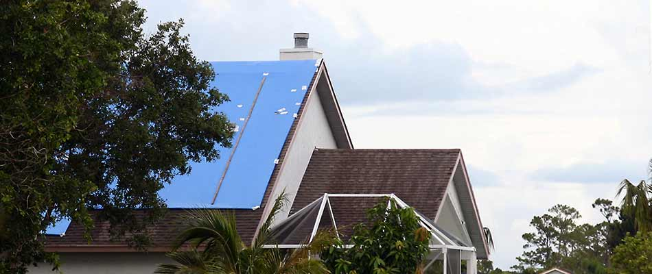 A home with a blue tarp applied over roof damage in Plant City, FL.