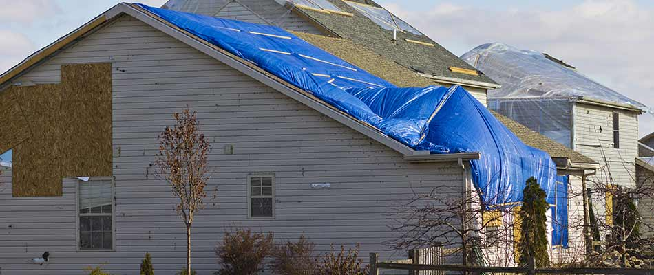 A storm damaged home with a blue tarp covered roof in Winter Haven, FL.