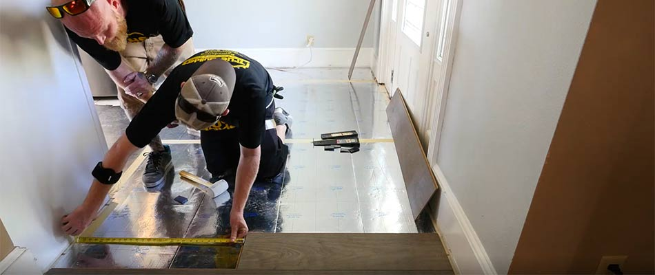 True Builders team members in the process of installing new flooring during a kitchen remodel in Dover, FL.