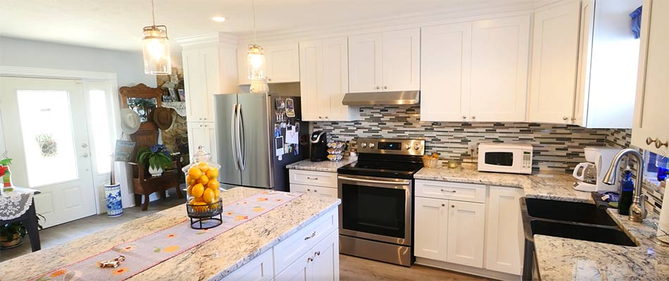 Overall view of a kitchen remodel that features an island and granite countertops, done by True Builders for homeowners in Dover, FL.